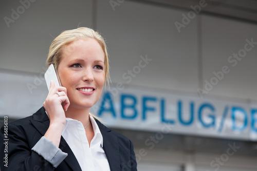 Frau telefoniert mit Handy am Flughafen