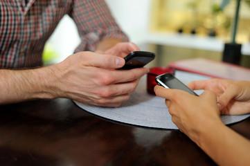 Smartphones und Hände im Restaurant