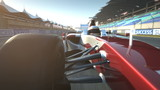 formula one race car speeding along home stretch and past camera