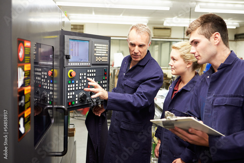 Engineer Teaching Apprentices To Use Computerized Lathe - 56858937