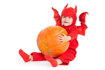 little boy in red devil costume sitting and holding big pumpkin