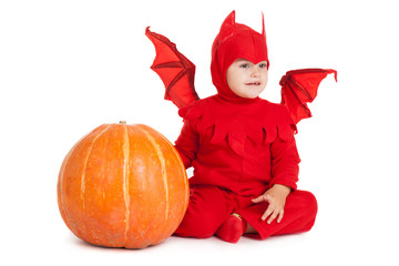 little boy in red devil costume sitting near big pumpkin