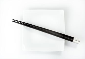 chopsticks on a plate isolated on a white background