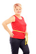 Smiling mature woman measuring her waist after diet