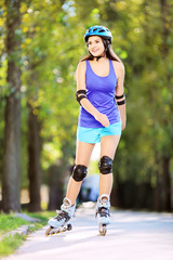Young smiling female on rollers skating in a park