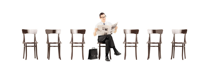 Young businessman sitting on a chair and reading a newspaper