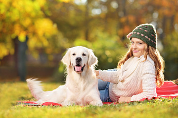 Young female on a grass with her labrador retriever dog in park