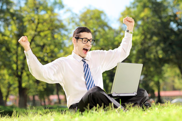Young man screaming and watching TV on a laptop in a park