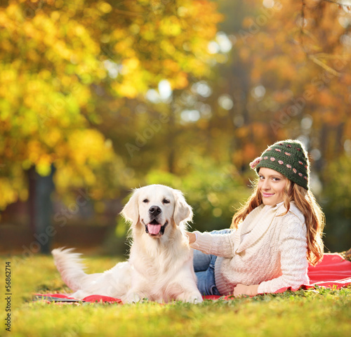Pretty female lying down with her labrador retriever dog in a pa