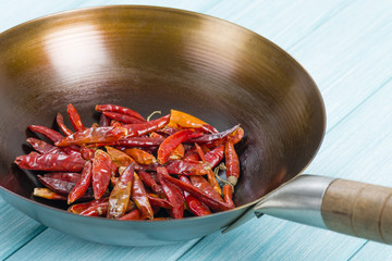 Red Dried Chillies - Dry chillies in a wok on a blue background.