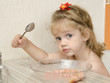 Ребенок с вопрошающим видом ест кашу