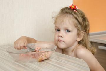 Ребенок с грустным видом ест кашу