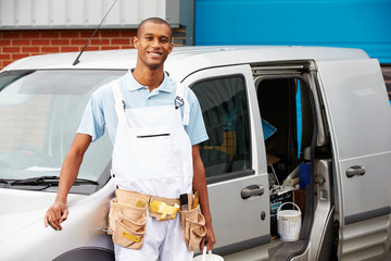 Decorator Wearing Overalls Standing Next To Van