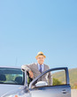 Smiling mature gentleman with hat posing next to his car