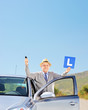 Smiling mature man posing next to his car holding a L sign