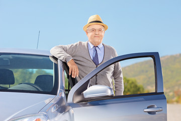 Smiling mature gentleman with hat posing next to his car outside