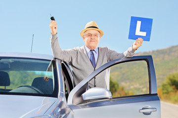 Smiling senior man posing next to his car holding a L sign