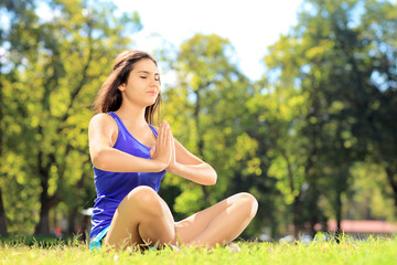 Young female athlete in sportswear doing yoga exercise in park