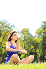 Young female athlete in sportswear doing yoga on a grass