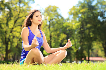 Young female athlete in sportswear meditating in a park