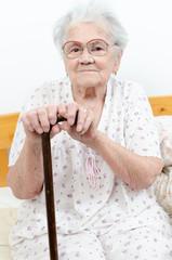 Senior woman portrait, on grey background with walking stick
