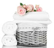 Bedding sheets in wicker basket isolated on white