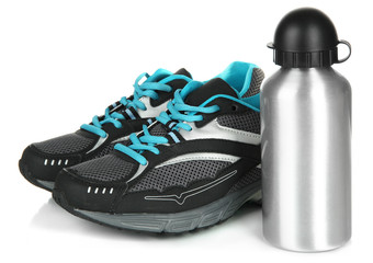 Sports bottle and sneakers isolated on white