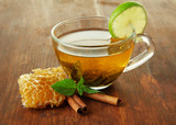 Transparent cup of green tea with honey and cinnamon