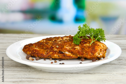 Roasted chicken fillets on white plate on bright background