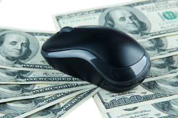 Computer mouse on dollars close up