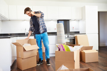 Man Moving Into New Home Talking On Mobile Phone