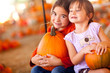 Adorable Little Girls Holding Pumpkins At A Pumpkin Patch