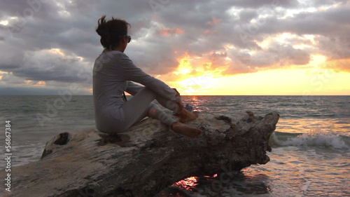 Woman sitting on a tree trunk enjoying the sunset