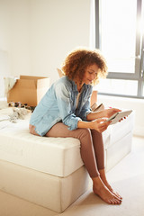 Woman Moving Into New Home Using Digital Tablet