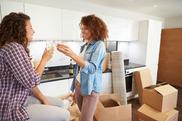 Two Women Celebrating Moving Into New Home With Champagne