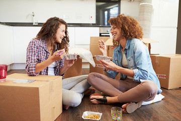 Two Women Moving Into New Home Enjoying Takeaway Meal