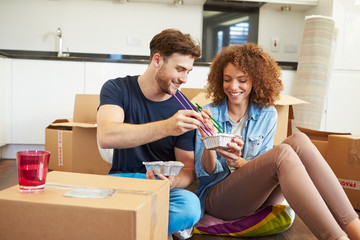 Couple Moving Into New Home Enjoying Takeaway Meal