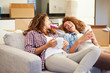 Two Women Relaxing On Sofa With Hot Drink In New Home
