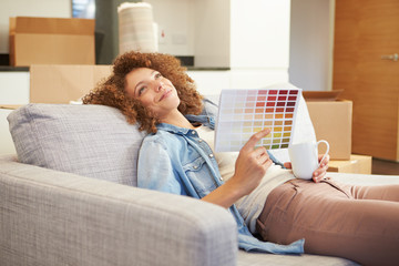 Woman Sitting On Sofa Looking At Paint Charts