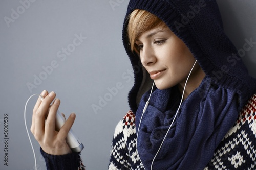 Young woman talking on phone using earbuds