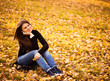 young woman sits on leaves in autumn park
