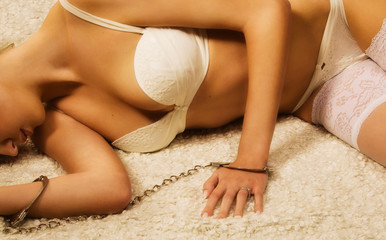 Beautiful  woman in handcuffs lying on a floor