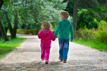 Little brother and sister walking by footpath