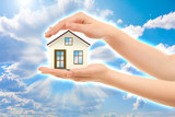 Picture of woman's hands holding a house against sky