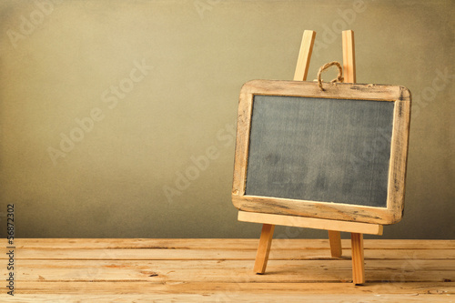 Chalkboard on wooden easel on wooden table