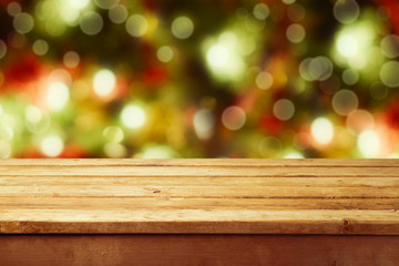 Christmas background with empty wooden table over bokeh