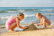 Adorable little girls playing at the seashore