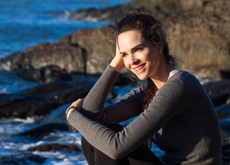 Happy woman sitting on the coast