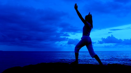 Silhouette Yoga woman in blue sky morning on sea beach