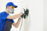 worker with orbital sander at wall filling poster
